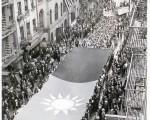 1938年5月12日,纽约华侨抗日大游行,队伍最前方是200名穿着旗袍的华裔妇女,侨胞纷纷捐款捐物,有的人从楼上把包好的钱一包包地投到国旗中间,照片上方飘扬的中美两幅国旗所在就是中华公所的旧址。(中华公所主席伍锐贤提供图片)