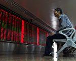 2015年7月10日,一位中国股民在北京一家证卷公司观看股市走势。(GREG BAKER/AFP/Getty Images)