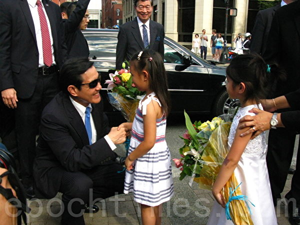 中华民国总统马英九蹲下来,与献花的中华广教学校学生握手致谢。(冯文鸾/大纪元)