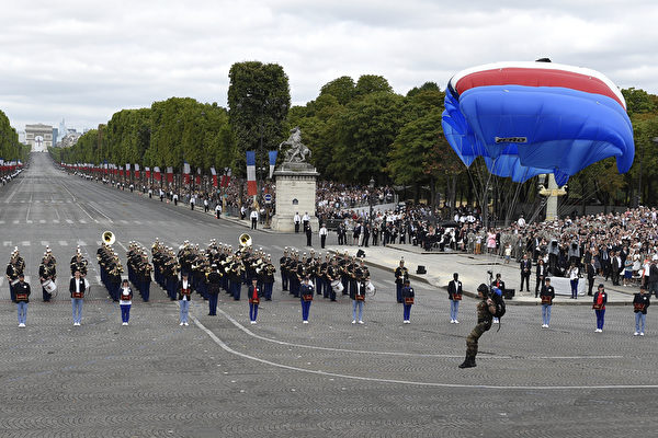 7月14日,法国国庆阅兵途中一名伞兵从天而降。(ALAIN JOCARD/AFP)