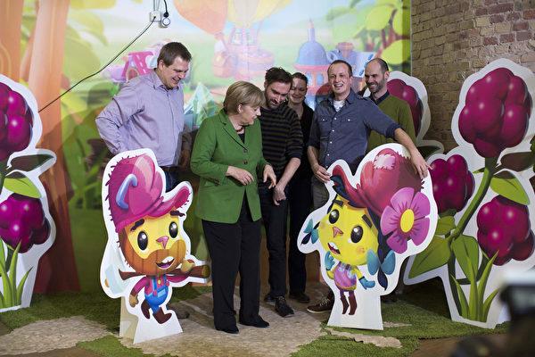 B著名的游戏开发公司Wooga也是柏林创业公司中的佼佼者。图为2013年3月7日默克尔总理到访该公司。(Carsten Koall/Getty Images)