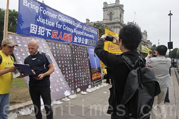 大陸遊客對著真相展板拍照。(李景行/大紀元
