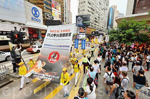 法輪功學員19日舉行7.20聲援起訴江澤民大遊行,從北角到中聯辦,沿途吸引許多民眾觀看。(宋祥龍/大紀元)