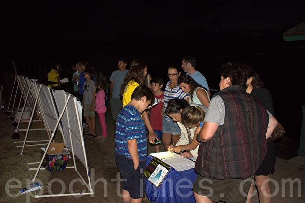 日落之际,法轮功学员开始烛光夜悼,吸引游人驻足。游人利用手机照明在制止活摘器官的征签板上签名。(杨婕/大纪元)