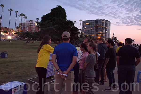 日落之际,法轮功学员开始烛光夜悼,吸引游人驻足。(杨婕/大纪元)