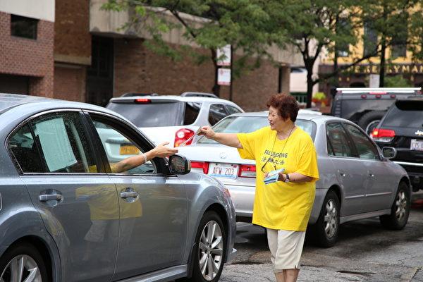 2015年7月18日,部分大芝加哥地區法輪功學員在芝加哥中領館前集會。圖為路過的行人向法輪功學員索取資料。(王松林/大紀元)