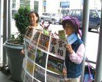 2015年7月15日,纽约曼哈顿帝国大厦门前,从大陆流亡海外的法轮功学员李敏(右)和葛荣贞(左)手举真相展板。(张小清/大纪元)