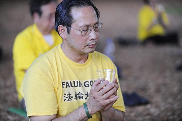 奥兰多法轮功学员阮清先生在悼念被中共迫害致死的法轮功学员 (岑华颖/大纪元  )