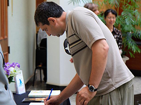 来市政厅办事的民众看完美展后,纷纷在留言簿上签名。  (赵琪/大纪元)