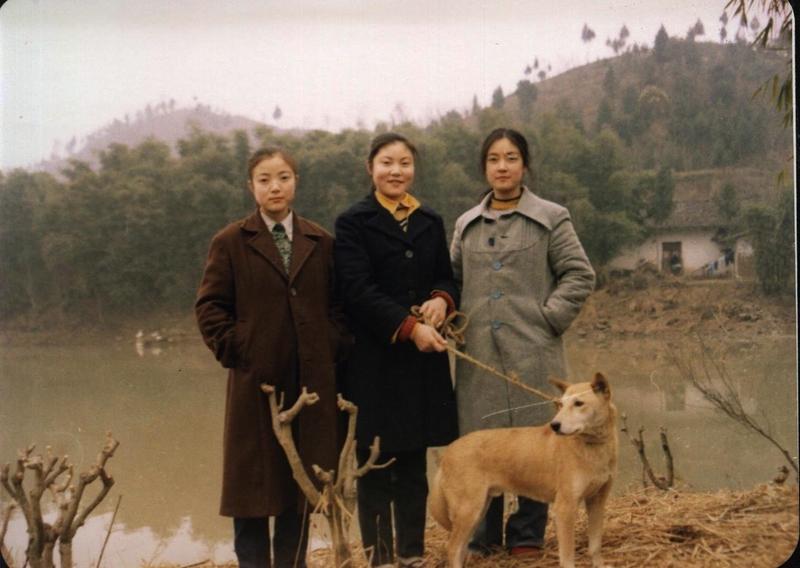 1980年代,作者(右一)與兩個妹妹攝於中江朝中老家。身後即為祖輩留下的土墻屋。(作者提供)