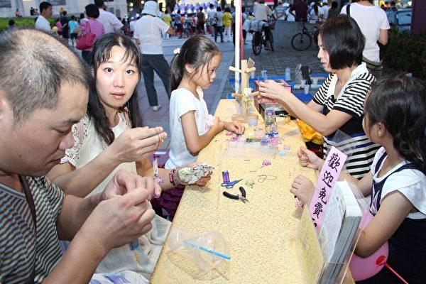 莲花DIY教作,民众都很喜欢学作莲花。(李撷璎/大纪元)