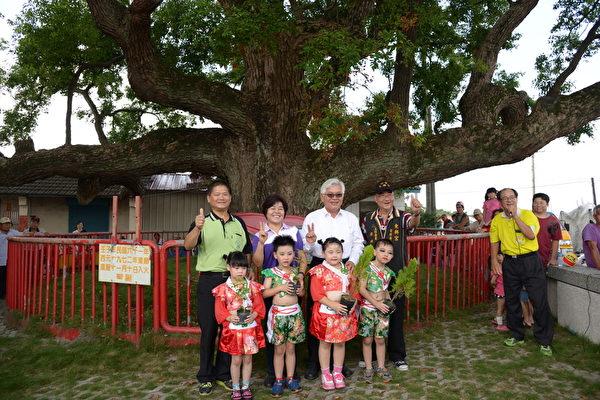 县长李进勇、乡长廖秋蓉分送树苗给小朋友,象征老树的传承。(云林县府提供)