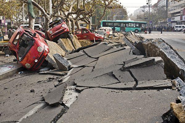 2013年11月22日凌晨2时许,山东省青岛市中石化黄潍输油管线一输油管道发生原油泄漏。上午10时许,在抢修的过程中,管道破裂处起火引发大爆炸,升起黑色蘑菇云。图为爆炸现场,汽车被炸飞倒在路边。(STR/AFP/Getty Images)