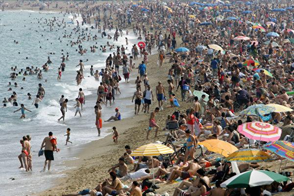西班牙巴塞羅那海灘戲水遊客。(LLUIS GENE/AFP)