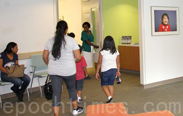 各具個性的肖像照掛到兒科及婦幼保健中心候診區的牆上,給來院兒童創造了一個放鬆的環境。(蔡溶/大紀元)