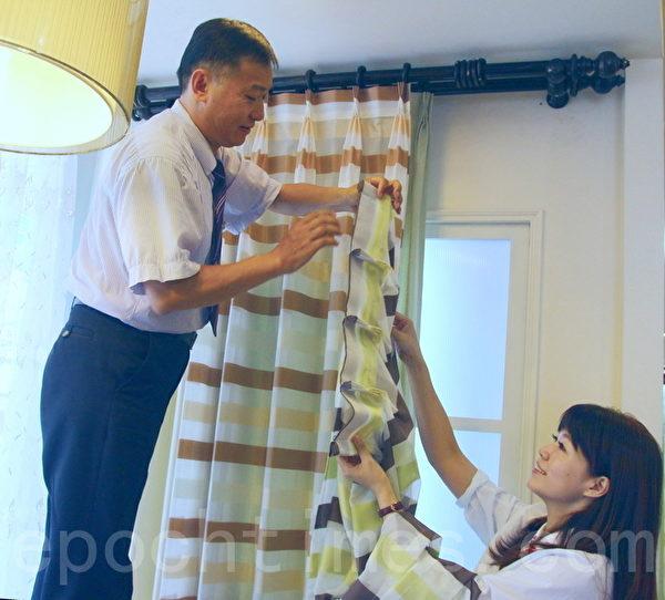 隆美仁德門市店長黃振財(左)將同系列的窗簾掛上,好讓顧客做比較。(賴友容/大紀元)