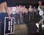 2015年8月9日,在密苏里州弗格森举行的纪念遭白人警察击毙的黑人少年布朗的活动上,抗议的民众与警察对峙。(Scott Olson/Getty Images)