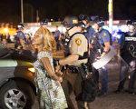 佛格森原本平和的周年游行,10日却因1名男子和警方交火,遭警方严重射伤,引发居民和警方紧张对峙而变调。(Scott Olson/Getty Images)