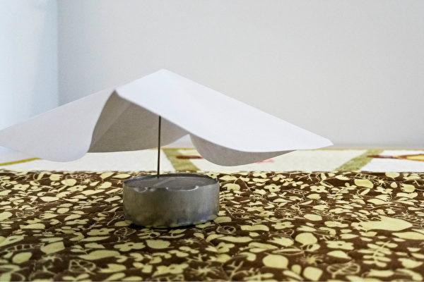 金字塔型紙張置於針的上方。(Tara MacIsaac/大紀元)