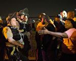 2015年8月10日,美国密苏里州佛格森市,为纪念非裔青年布朗遭白人警察击毙一周年的示威活动,但活动不时传出暴力行为。图为群众与警察紧张对峙。(Scott Olson/Getty Images)