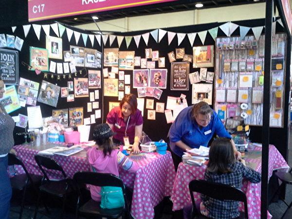 在卡片制作摊位上,孩子们在工作人员Isobel Logan和 Amarylise Bessey 的帮助下学习制作创意卡片。(李凤贞/大纪元)