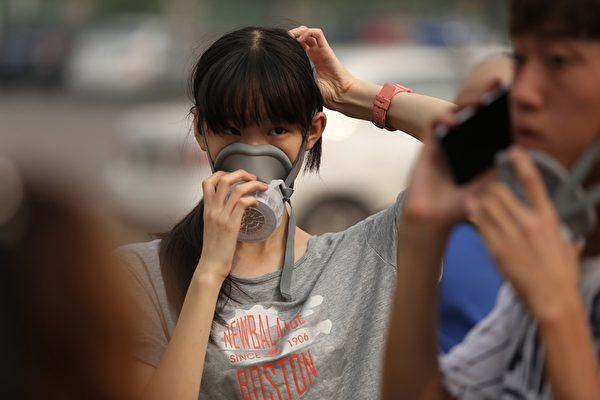 2015年8月14日,天津大爆炸后,民众纷纷戴上防护口罩。(STR/AFP/Getty Images)