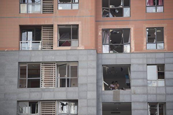 2015年8月13日,事故周边1公里范围内许多住宅楼满目疮痍,面向爆炸方向的大楼窗户几乎都难幸免。(FRED DUFOUR/AFP/Getty Images)