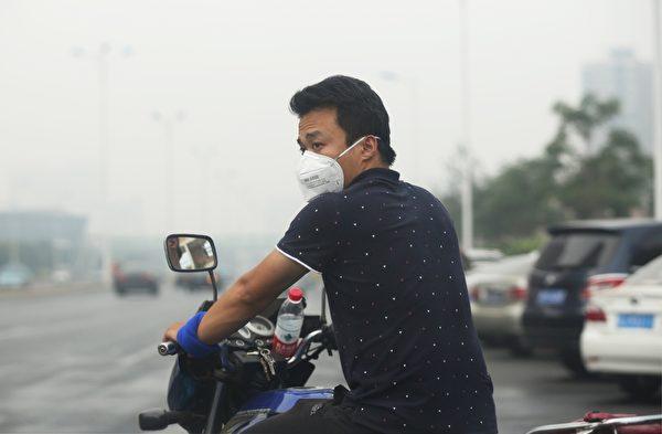 2015年8月14日,天津爆炸事故地点附近的街道上,民众纷纷戴上防护口罩。(STR/AFP/Getty Images)