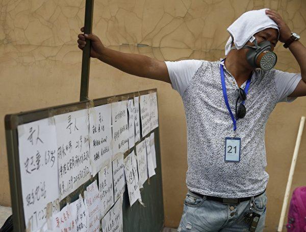 2015年8月15日,天津爆炸事故地点附近,民众纷纷戴上防护口罩。(STR/AFP/Getty Images)
