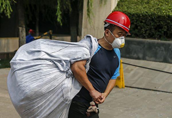 2015年8月15日,天津爆炸事故地点附近的街道上,可见到民众纷纷戴上防护口罩。(STR/AFP/Getty Images)