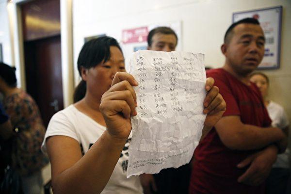 2015年8月15日,天津,在新闻发布会的会场,一位民众拿出写有失踪消防人员名字的文件。(STR/AFP/Getty Images)