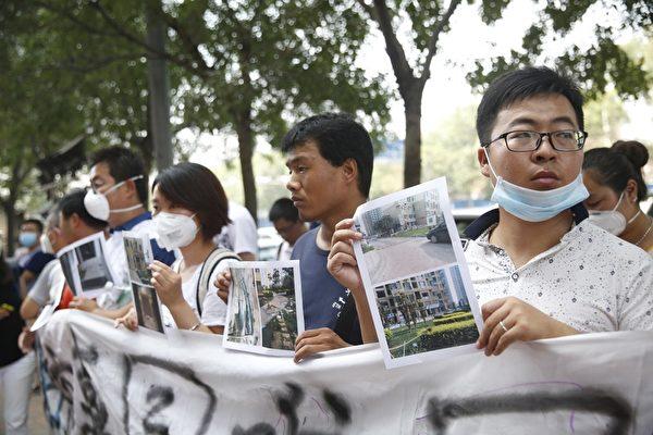 2015年8月16日,天津启航嘉园社区受害民众在新闻发布会场外抗议。(STR/AFP/Getty Images)