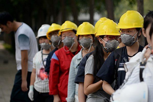2015年8月16日,天津爆炸事故地点附近的一家工厂员工,戴上防护口罩。(WANG ZHAO/AFP/Getty Images)