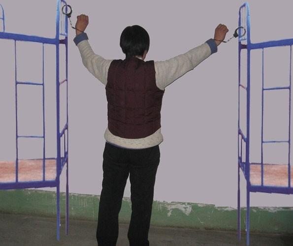 酷刑演示:吊拷在兩個高低床中間(明慧網)