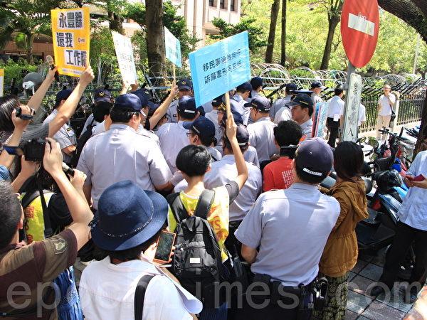 群众不满移民署回应,场面混乱,移民署官员则在警方引导下离开。(陈懿胜/大纪元)