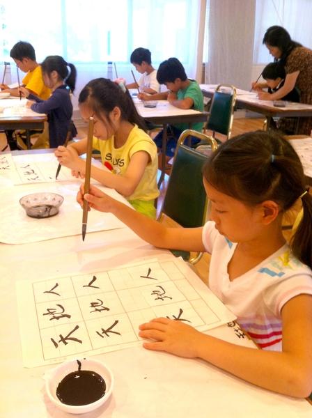 學生寫毛筆字。(明慧文化藝術中心提供)