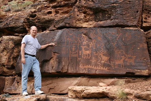 迄今为止,约翰‧拉斯坎普在亚利桑那州、犹他州、内华达州、加州、俄克拉荷马州等共发现84处与中国古代文字相对应的石刻文。图为拉斯坎普在犹他州九英里峡谷的石刻文之前留影。(Courtesy of John Ruskamp)