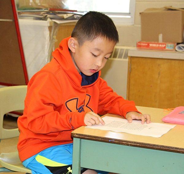 今年六岁的殿殿认真读《论语》。(明慧网)