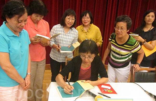 《前所未有的邪恶迫害》全球首发记者会23日于台大举行,作者之一台大新闻所教授张锦华为读者在新书上签名留念。(钟元/大纪元)