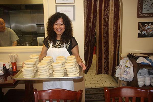 图:肉夹馍是陕西的名吃。姗姗面馆老板娘Lili 端著一大盘新烤的馍出来,又香又鲜。(王百合/大纪元)