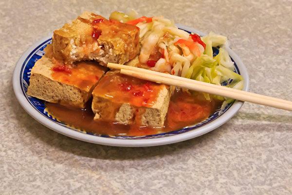 評委表示,第一次品嚐臭豆腐的體驗很矛盾,需克服刺鼻怪異味道,令人感到煎熬和可怕,但入口後卻又激起迷人的慾望,滋味很難形容。(王嘉益/大紀元)