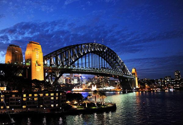 夜幕下的悉尼港,两个高12米的巨大钢筋水泥桥墩很显目。。(Greg WOOD/AFP)