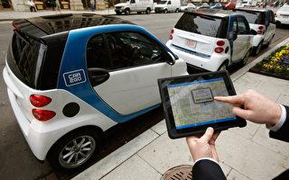 图为戴姆勒旗下的汽车共享服务car2go的员工正在示范如何使用智能装置叫车。(Chip Somodevilla/Getty Images)