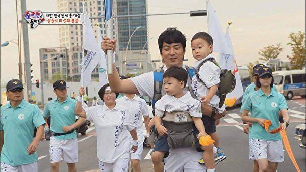 宋一國背三胞胎護送2014年亞運聖火。(中天提供)
