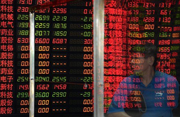 7月7日上午,兩市雙雙跳水。 圖為,2015年7月6日,上海一個公司外的股市行情電子板 。 (STR/AFP/Getty Images)