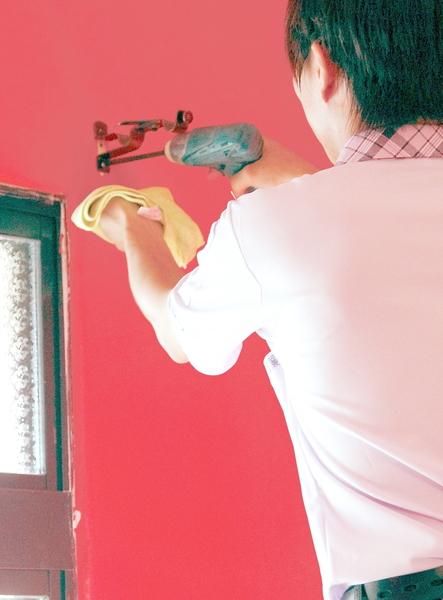 鑽孔時,安裝師傅手拿布謹慎接住泥灰, 服務真窩心。(圖:隆美窗簾提供)