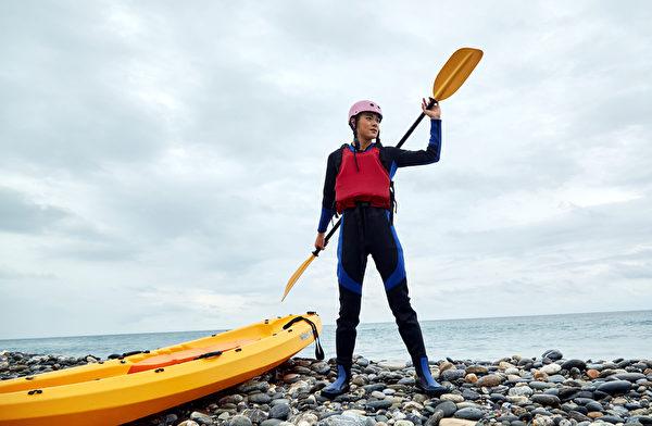 易恩在海邊耍寶擺起划獨木舟的架勢。(凱特文化提供)