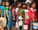 2015年9月7日,敘利亞兒童在北部城市阿勒頗排隊領取食物援助。敘利亞內戰造成20多萬人死亡,1,100萬敘利亞人流離失所,400萬成為難民,國際社會也深受影響。(Fadi al-Halabi/AFP/Getty Images)