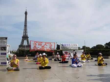 二零一五年九月七日,部份法國法輪功學員在艾菲爾鐵塔下的人權廣場集體煉功和傳播法輪功的真相,同時徵集制止中共活摘法輪功學員器官的簽名,及聲援訴江。(明慧網)