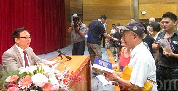 """著名历史学家辛灏年教授日前应邀在台大专题演讲""""二个中国与台湾命运的关系"""",会后辛灏年为购买新书《中国命运与台湾前途》的民众签名。(钟元/大纪元)"""